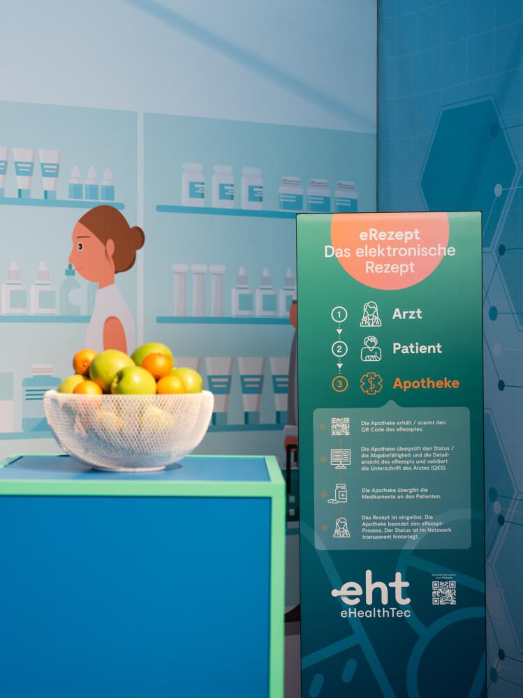 Rechts ein aufsteller zum E-Rezept, der den Ablauf bei der Apotheke genauer beleuchtet, links eine gefüllte Obstschale